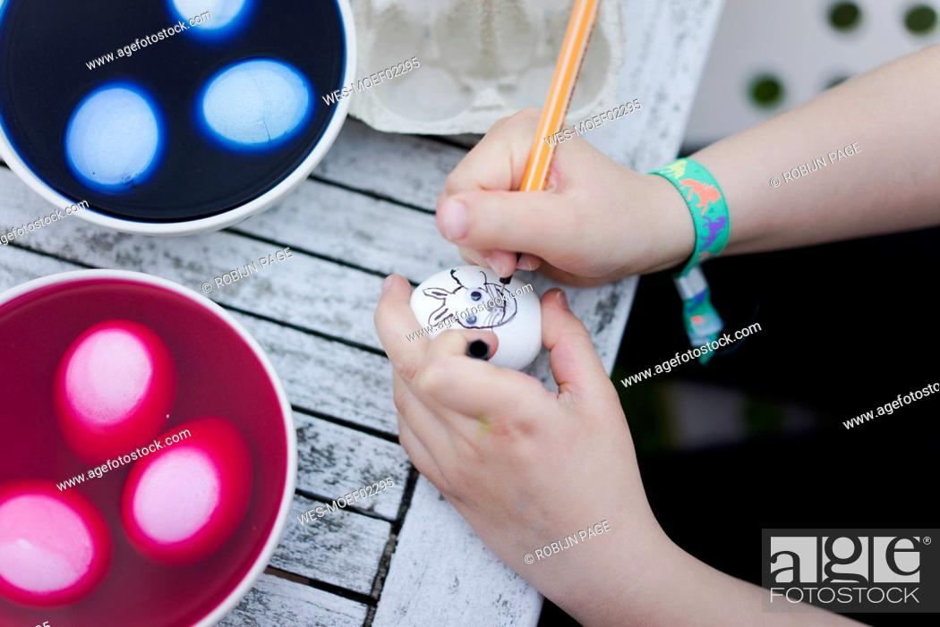 Stock Photo: Close-up of girl painting face on Easter egg on garden table.