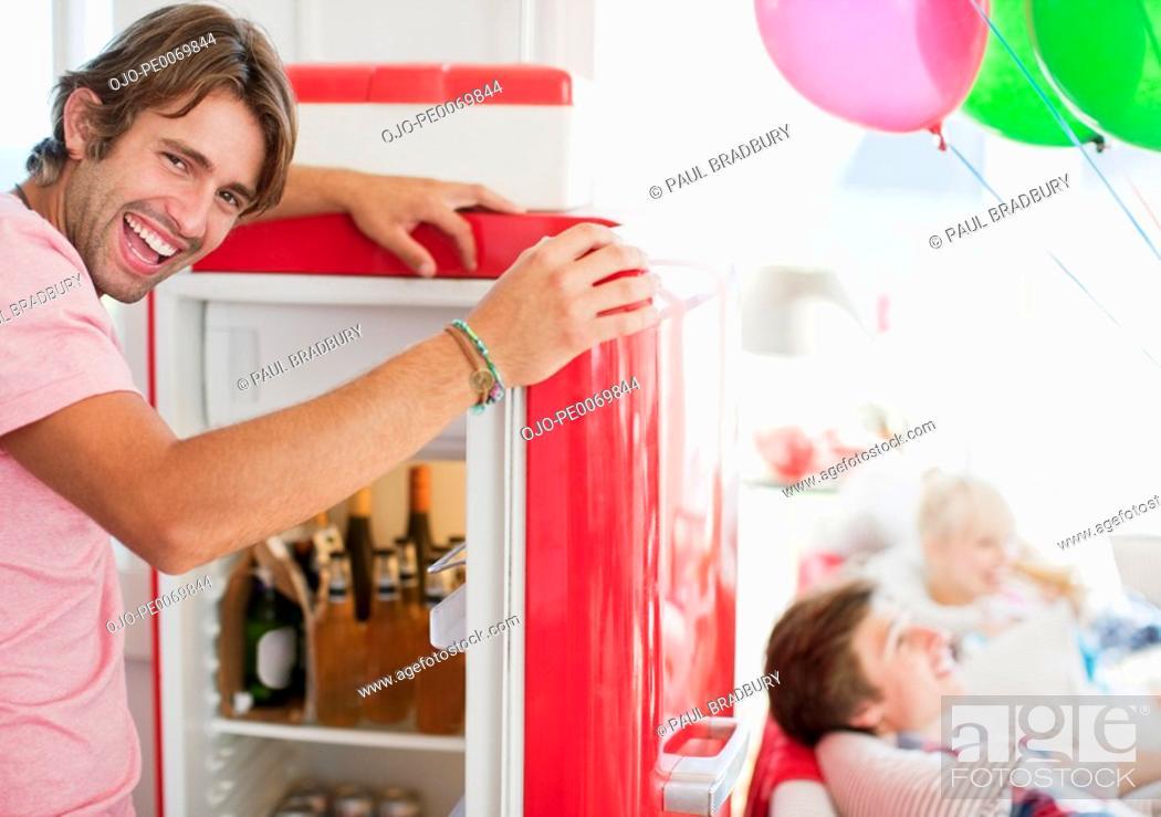 Stock Photo: Man opening refrigerator.