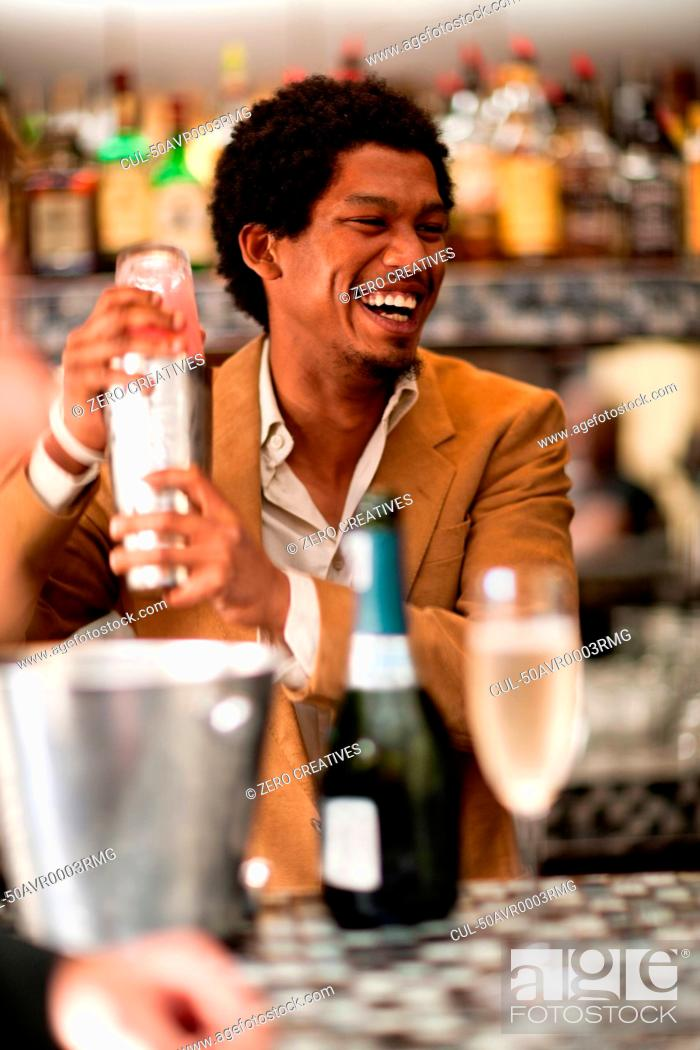 Stock Photo: Bartender mixing drinks at bar.
