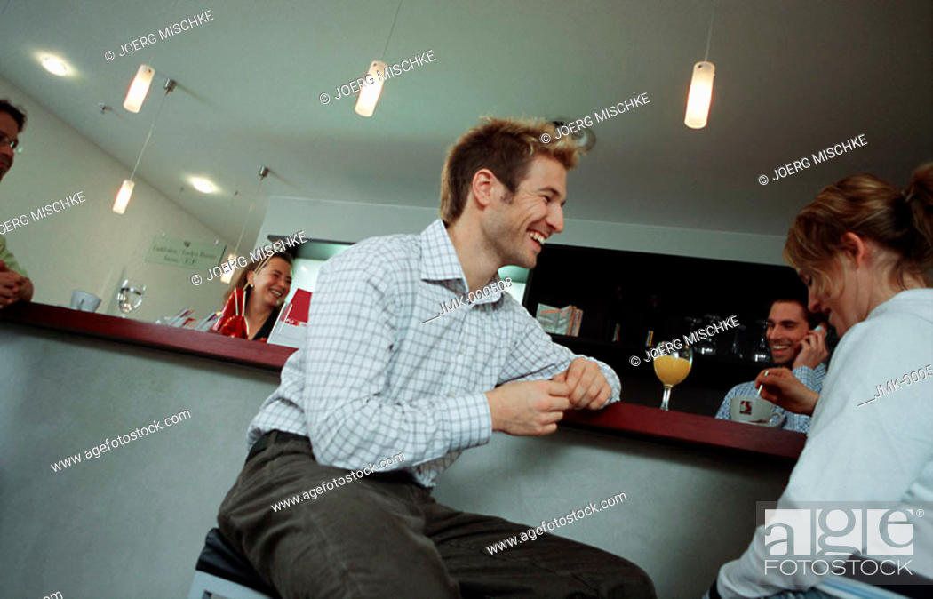 Stock Photo: Young man and young woman sitting at the reception of a gym, fitness center, talking.