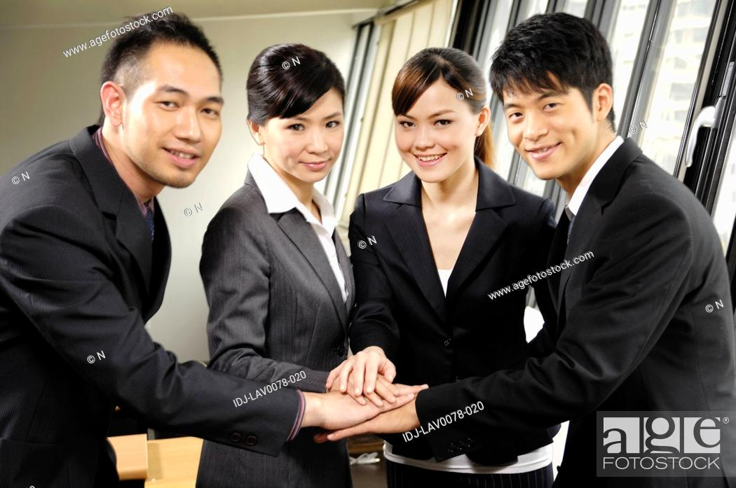 Stock Photo: Business executives stacking hands in an office.