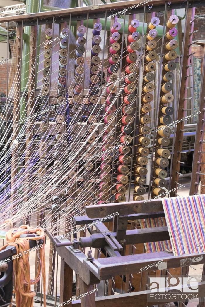 Imagen: Woosh of filmy threads from columns of stacked, brightly coloured wooden bobbins in traditional jacquard weaving manufacture, La Manufacture de Roubaix, France.