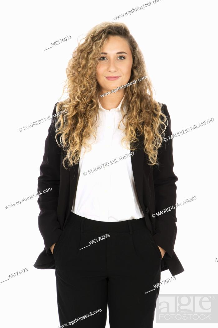 Stock Photo: Smiling girl with curly blonde hair, she is standing with her hands in her pocket, wearing a black suit and white shirt.