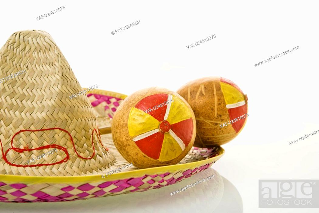 Stock Photo: Pair of handmade Mexican maracas percussion musical instruments on sombrero straw hat.