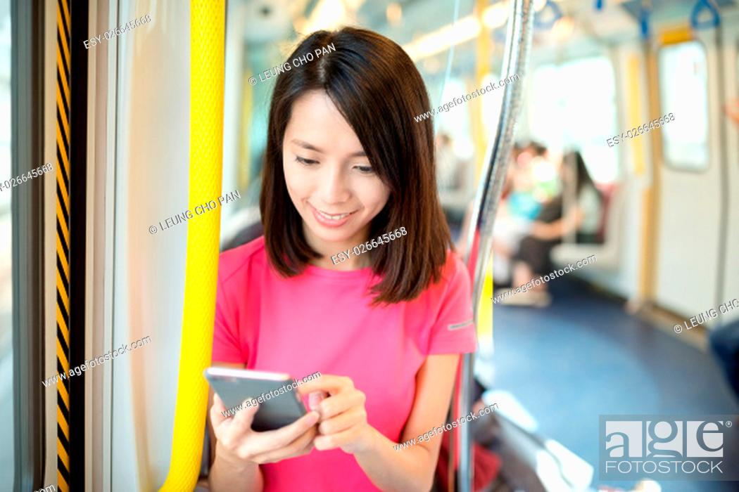 Stock Photo: Young woman looking at cellphone inside train compartment.
