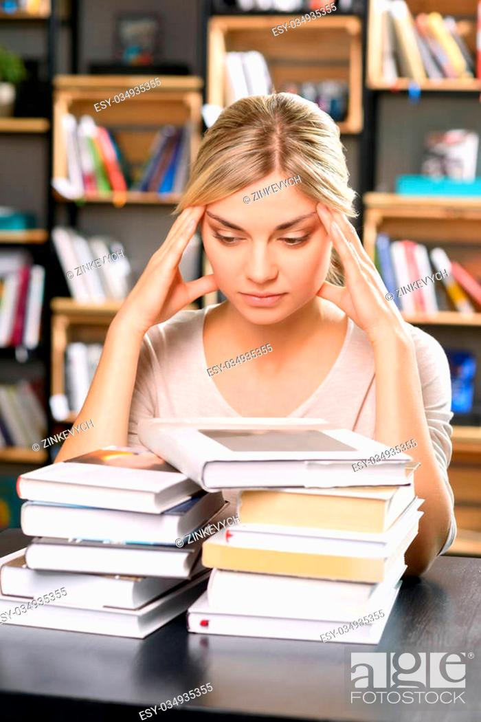 Stock Photo: Too much work. Nice looking girl looks tired while observing all the literature she has to look through.