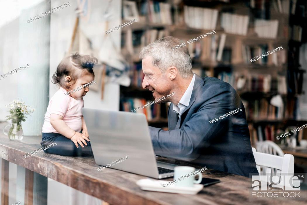 Stock Photo: Businessman with little daughter working on laptop in cafe.