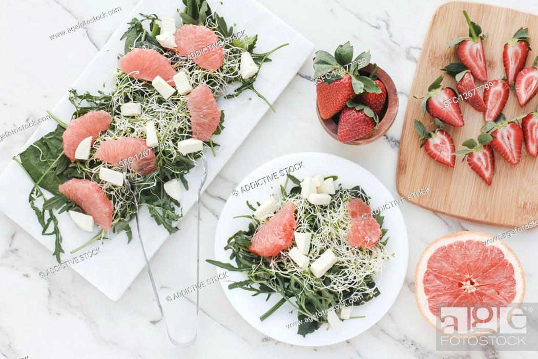 Imagen: Top view of bowls with strawberry, grapefruit and rocket salad on table served on kitchen boards.