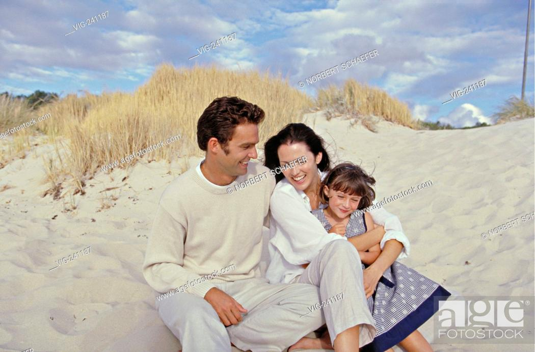 Stock Photo: portrait, brunette family wearing bright colours with their 5 years old daughter is sitting in tied embracement at the beach  - GERMANY, 27/01/2004.