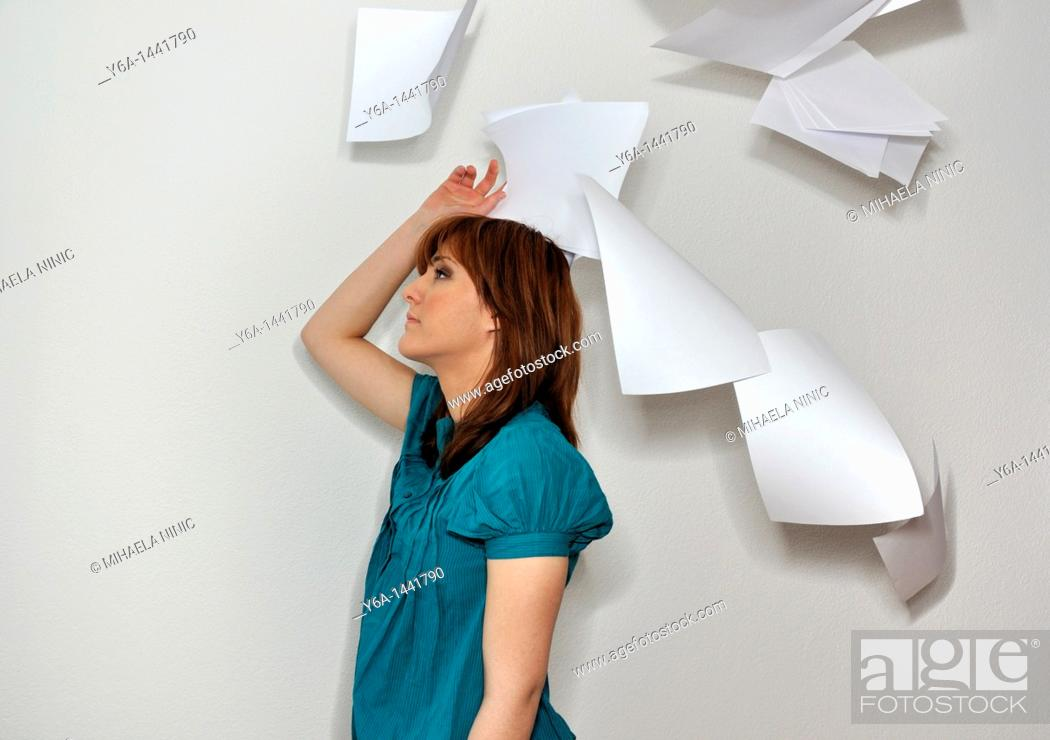 Stock Photo: Young woman throwing paperwork in air.