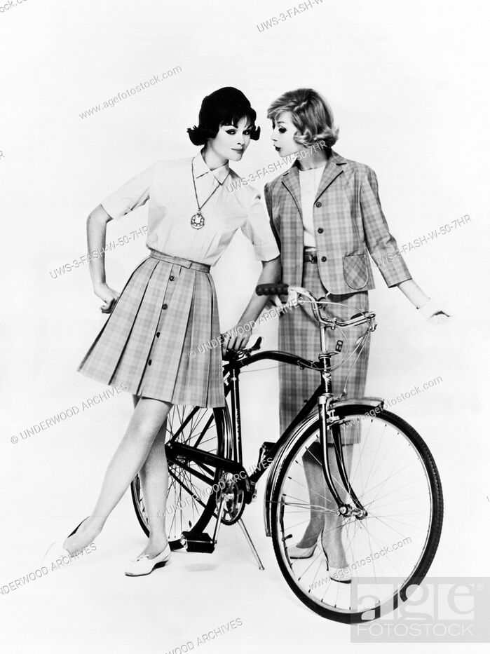 Stock Photo: United States: c. 1958 Two women with a bicycle model vacation fashions in cotton for traveling or sightseeing. They are styled by Miss Pat of California.