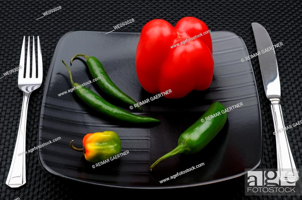 Stock Photo: Table setting with cutlery and black plate with sweet belll and hot chili peppers.
