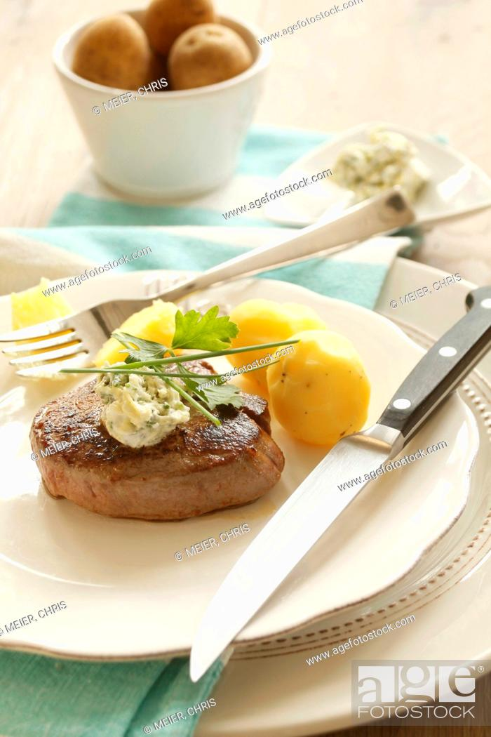 Stock Photo: Fillet steak with quark and herb butter and boiled potatoes.