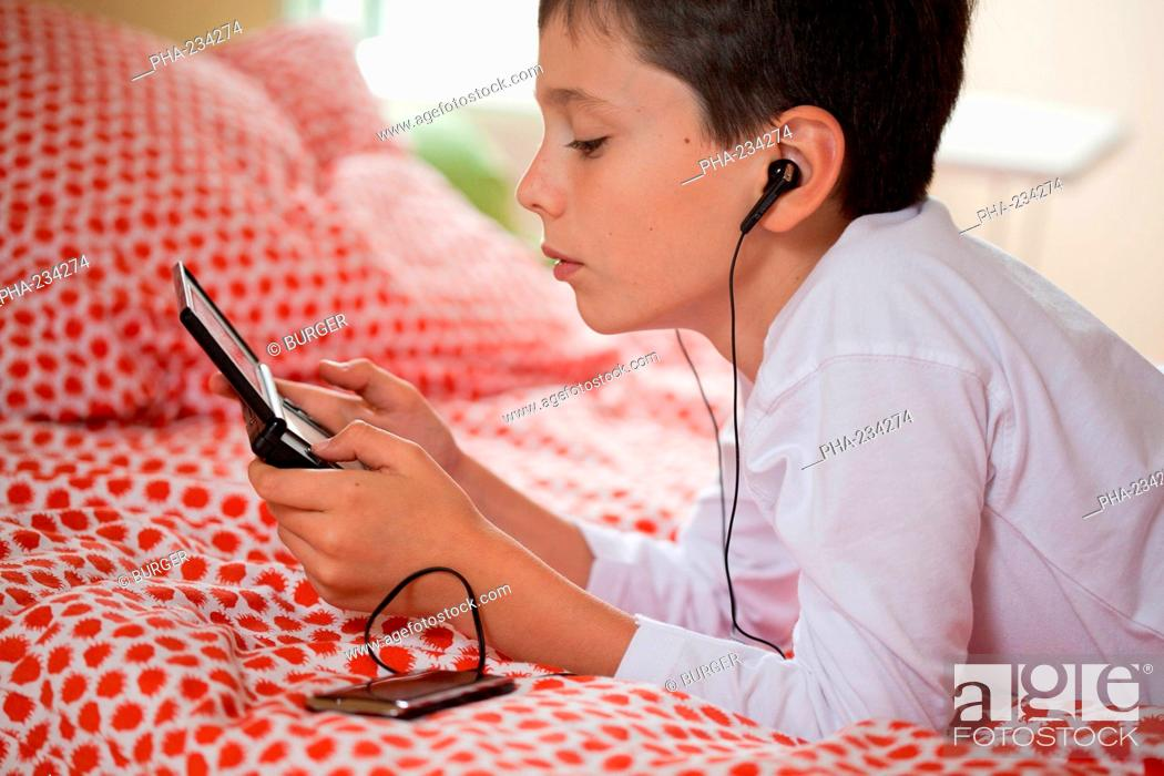 Stock Photo: 10 years old boy playing with video game console.