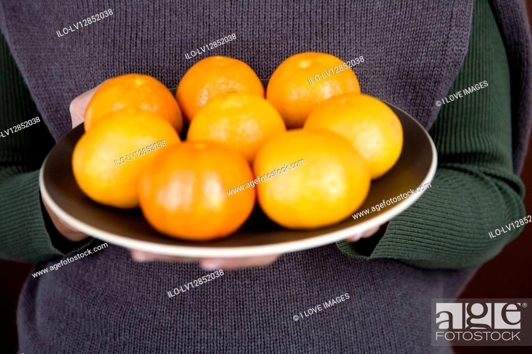 Stock Photo: A woman holding a plate of clementines.