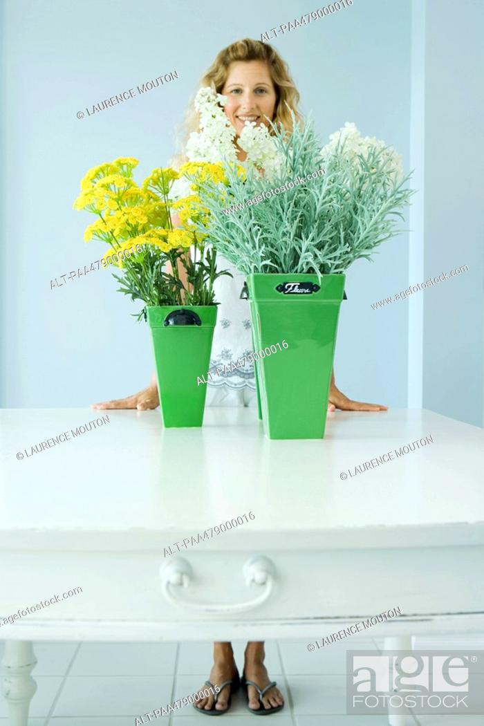 Stock Photo: Woman standing behind cut flowers, smiling, full length.