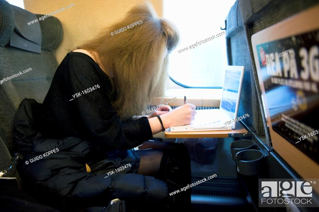 Stock Photo: A young, female Swedish student traveling by train from Sundsvall to Stockholm. She is using her laptop computer during the trip and she is just filling out the.