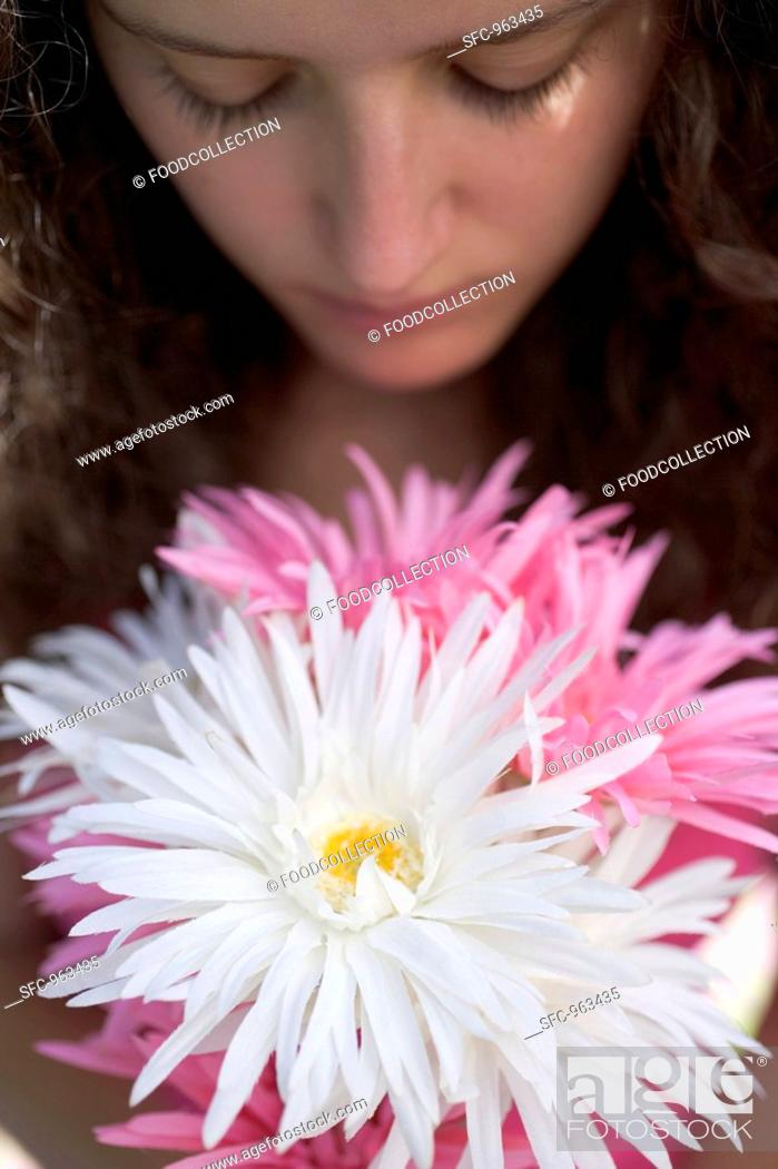 Stock Photo: Young woman with bunch of summer flowers.