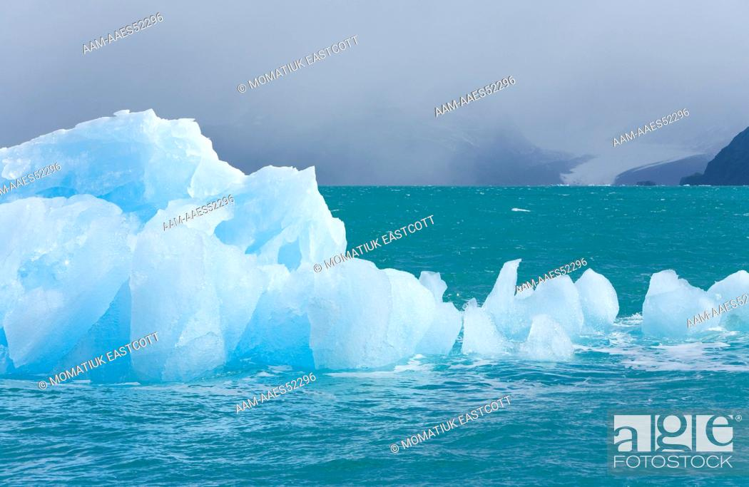 Imagen: Small blue iceberg calved from nearby glacier floating in calm sea and melting in unusually warm temperature signaling global warming, fall.