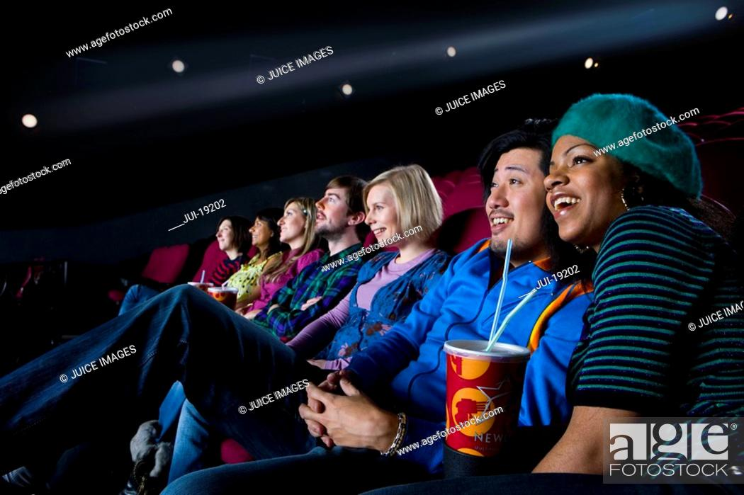 Stock Photo: Audience in cinema, girl with drink, smiling, low angle view.