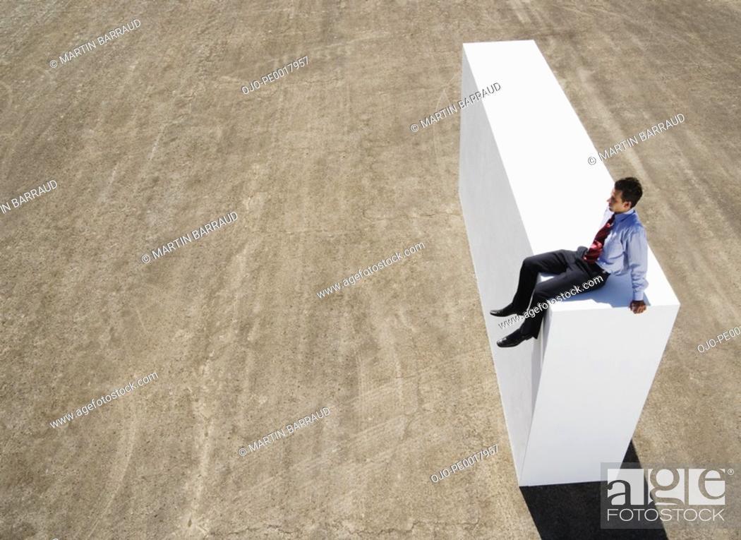 Stock Photo: Businessman sitting on block outdoors.