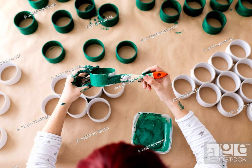 Stock Photo: Top view of woman's hands painting a roll of cardboard with a green brush.