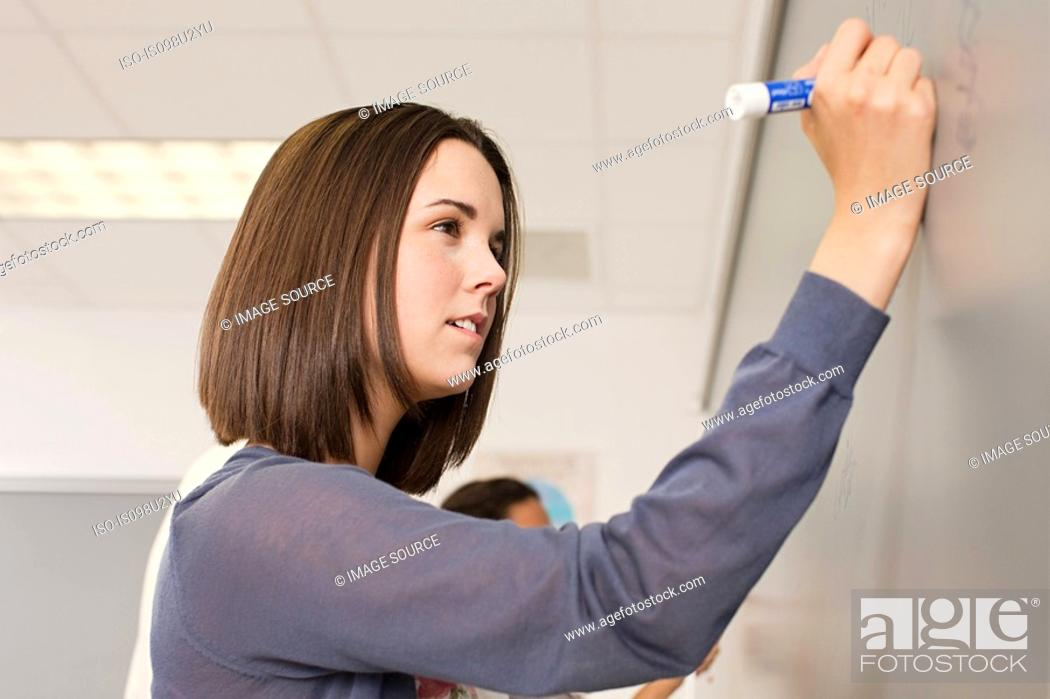 Stock Photo: Female high school student writing on white board.