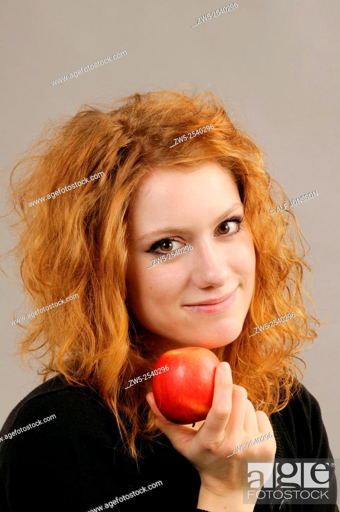 Stock Photo: Redhaired young woman with a red apple.