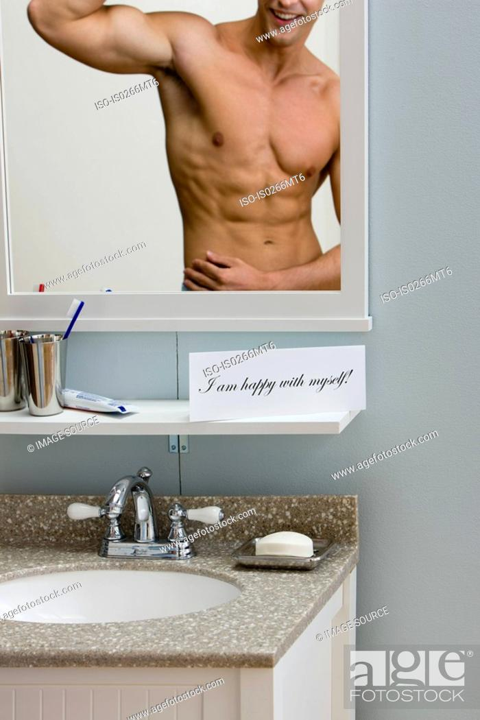 Stock Photo: A happy young man looking in a mirror.
