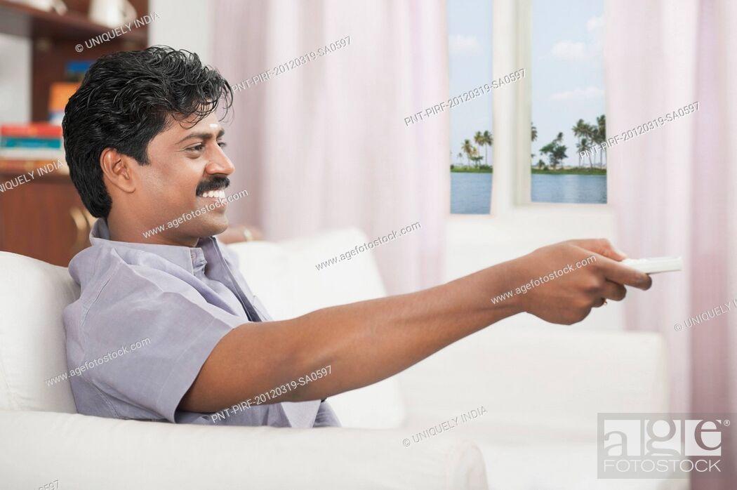 Stock Photo: South Indian man watching TV.