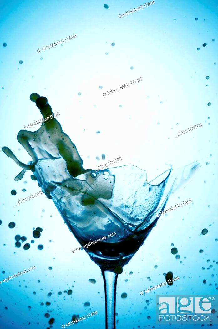 Stock Photo: Powerful Splash breaking a martini glass , a conceptual image about alcohol addiction.