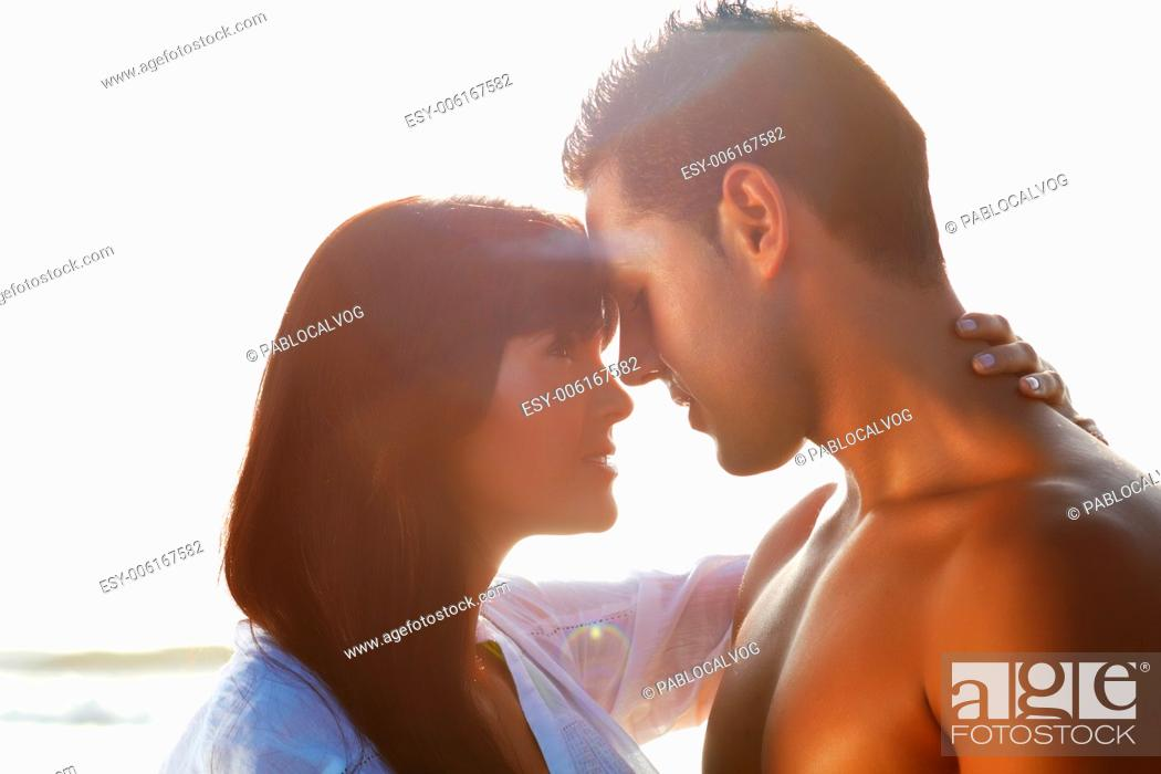 Stock Photo: portrait of a passionate couple in love kissing and embracing between backlit.