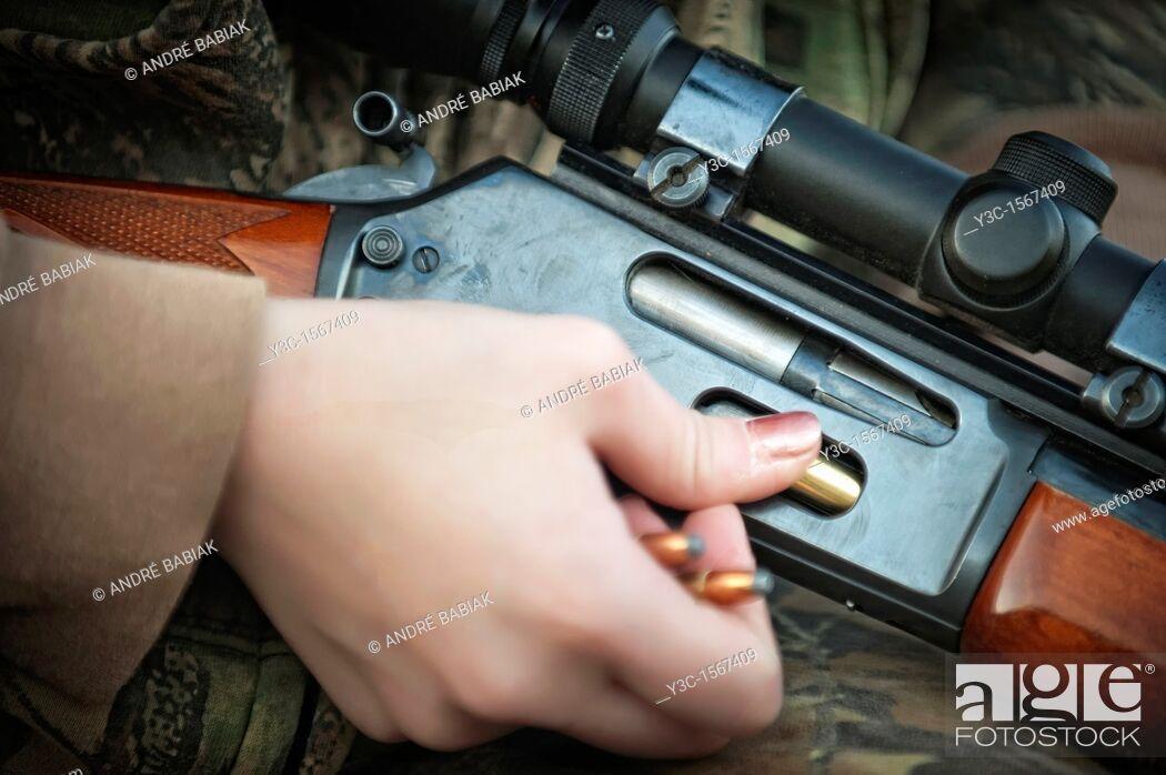 Stock Photo: Woman loading hunting rifle gun with 30-30 ammunition cartridges.