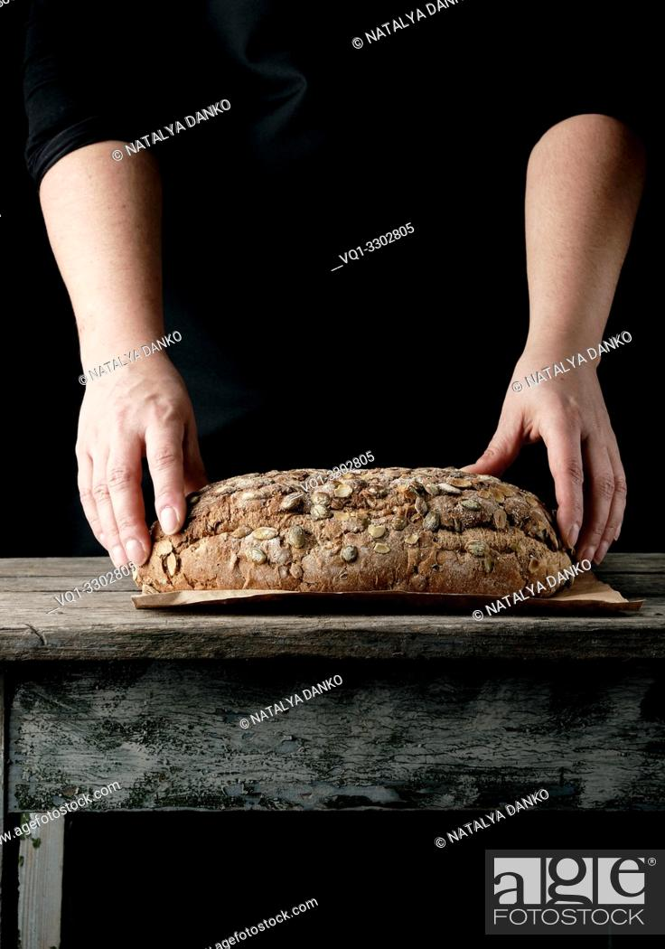 Stock Photo: female hands hold oval baked rye bread with pumpkin seeds, dark background.