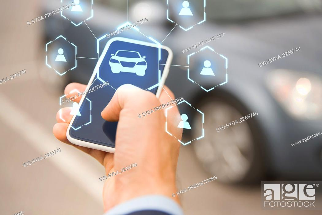 Stock Photo: businessman hand with smartphone car sharing app.