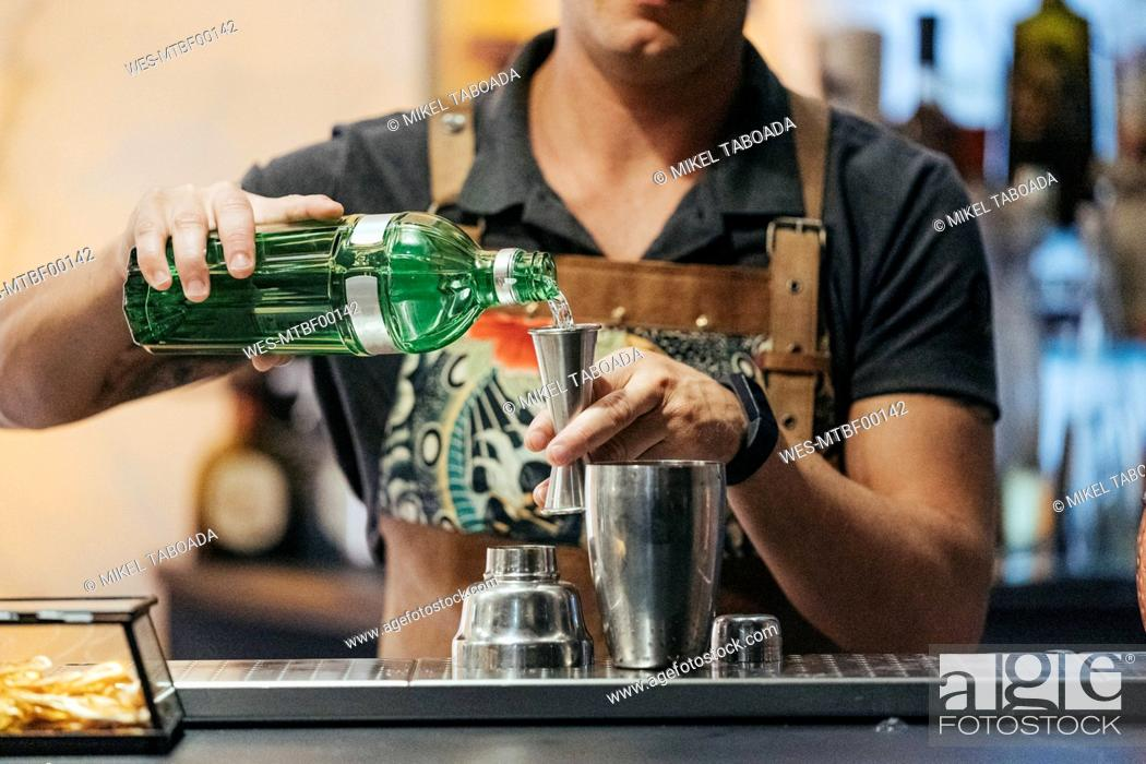 Stock Photo: Bartender mixing cocktail in a bar, using jigger.