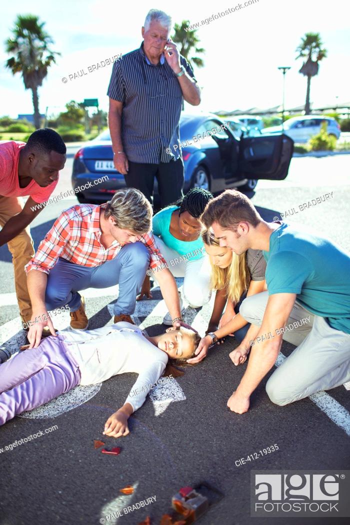 Stock Photo: People examining injured girl on street.