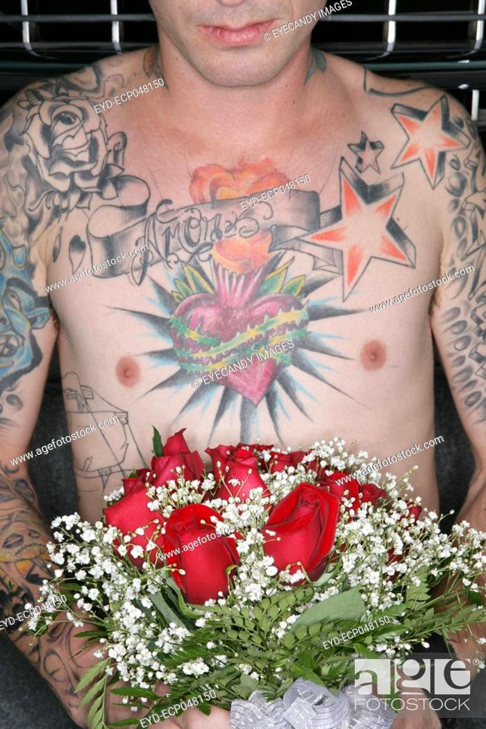 Stock Photo: Cropped view of a tattooed man holding a bouquet of roses.