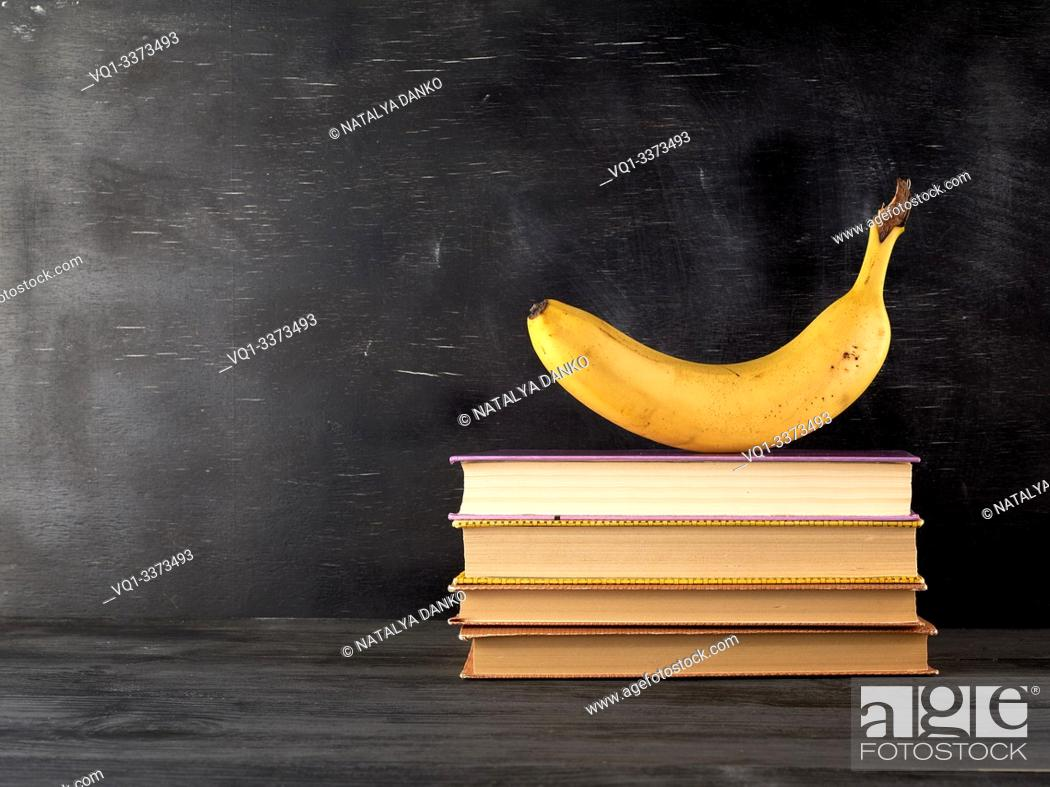 Stock Photo: closed books with yellow sheets and ripe banana on a black chalk board background, copy space, back to school concept.