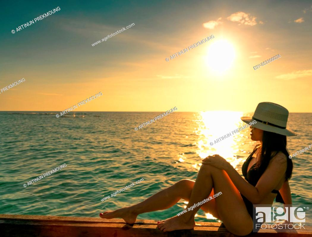 Imagen: Sexy and relax woman wear black bikini with straw hat sit on wooden beam near sand beach at sunset. Girl enjoy holiday at tropical paradise beach on summer.