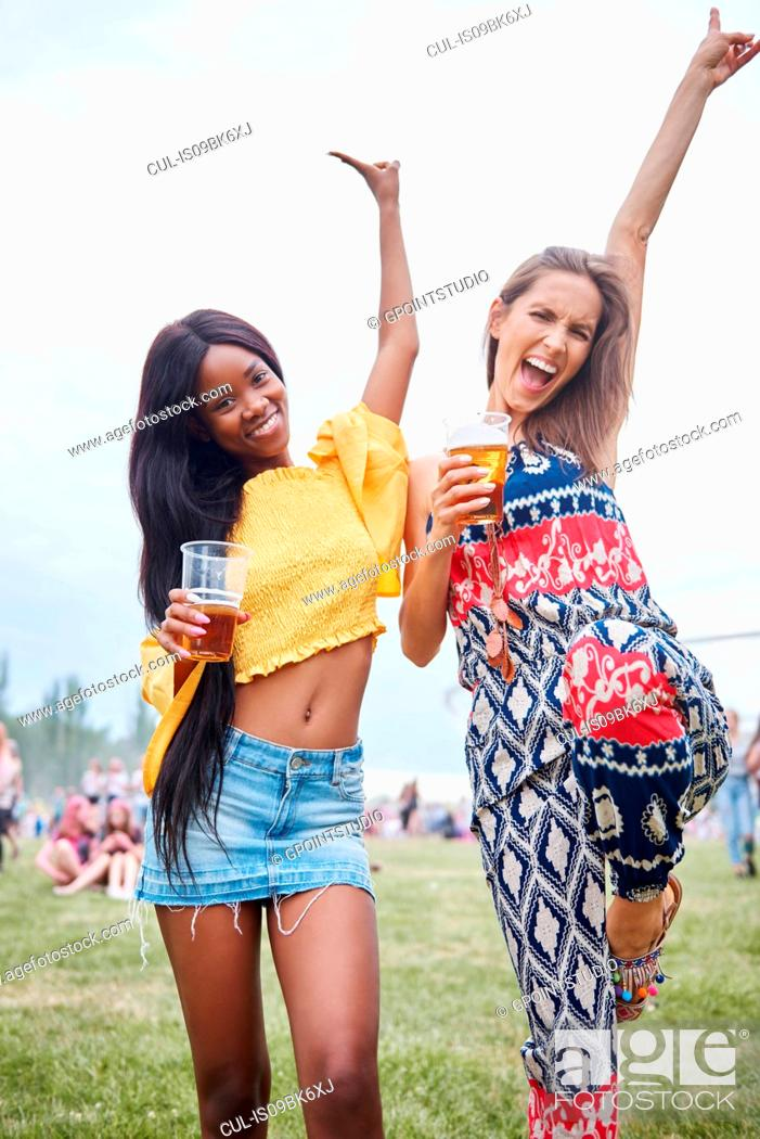 Stock Photo: Friends drinking and dancing with arms raised in music festival.