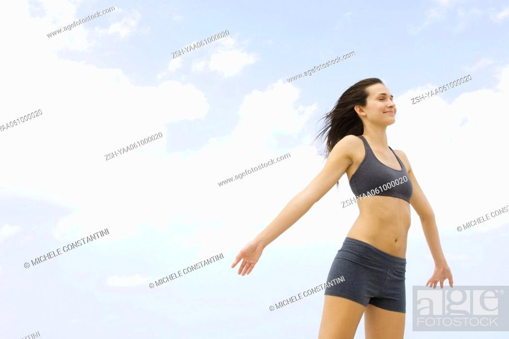 Stock Photo: Young woman in sports bra standing outdoors, arms out, eyes closed.