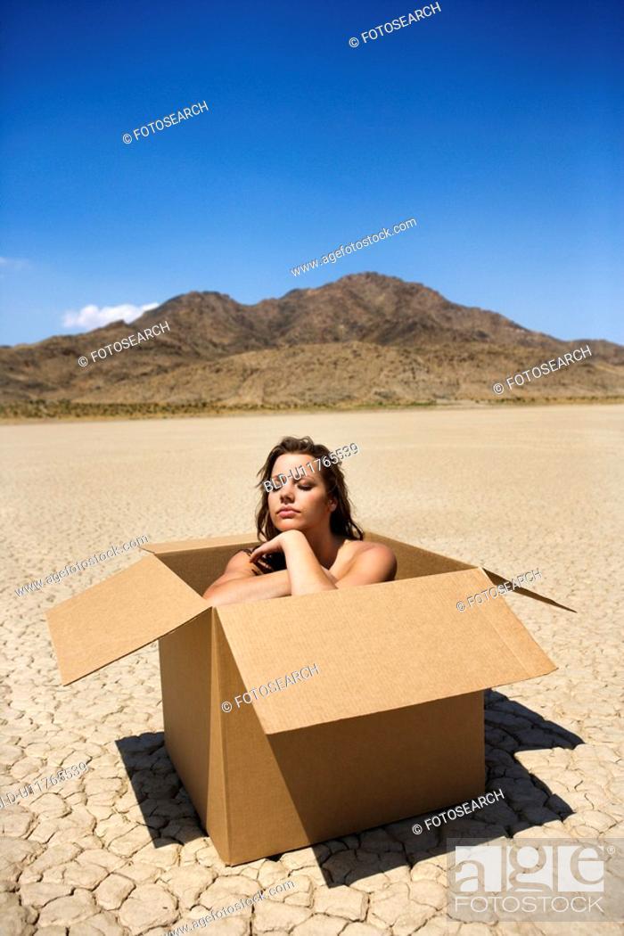 Stock Photo: Woman sitting in box in cracked desert landscape in California.