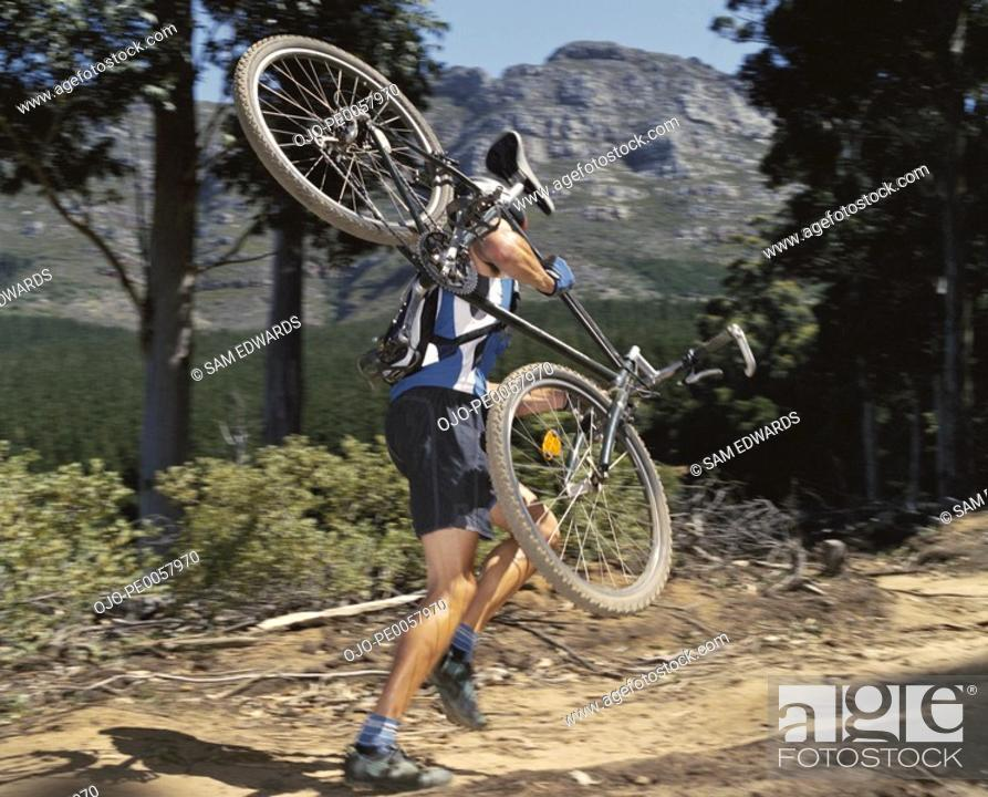 Stock Photo: A man carrying a mountain bike on a path.