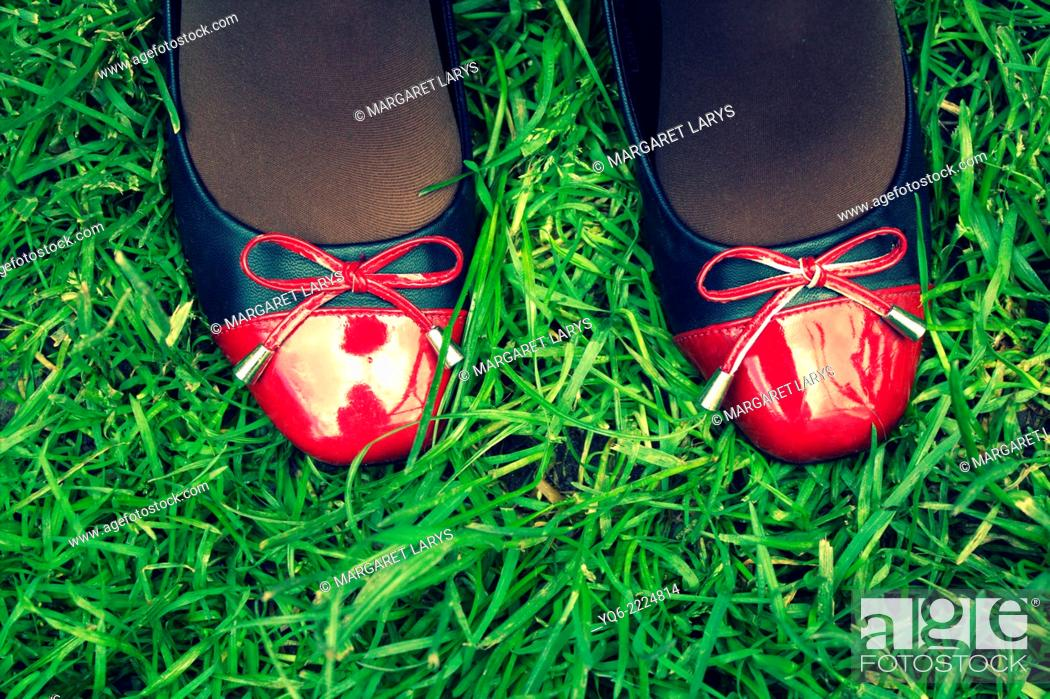 Stock Photo: A teenager's legs in red and black shoes on the grass.