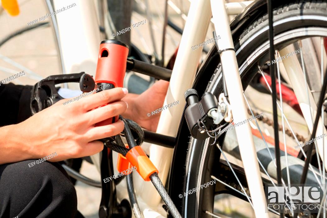 Photo de stock: Close-up Of Businesswoman's Hand Locking Up Her Bicycle.
