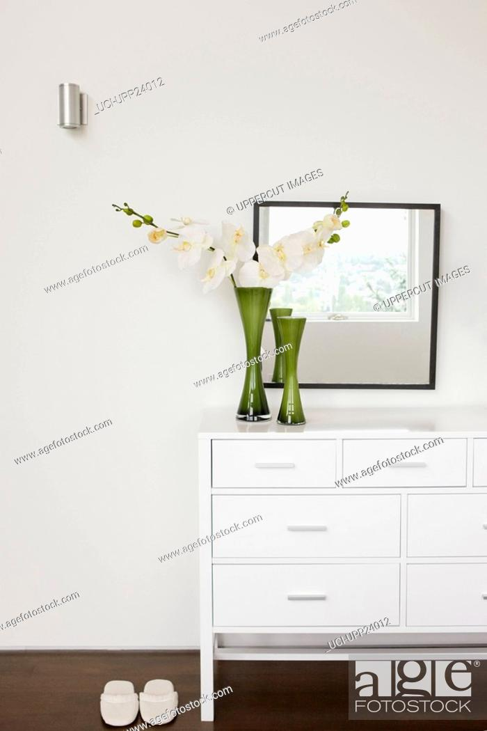 Stock Photo: Vase of flowers on bedroom dresser.