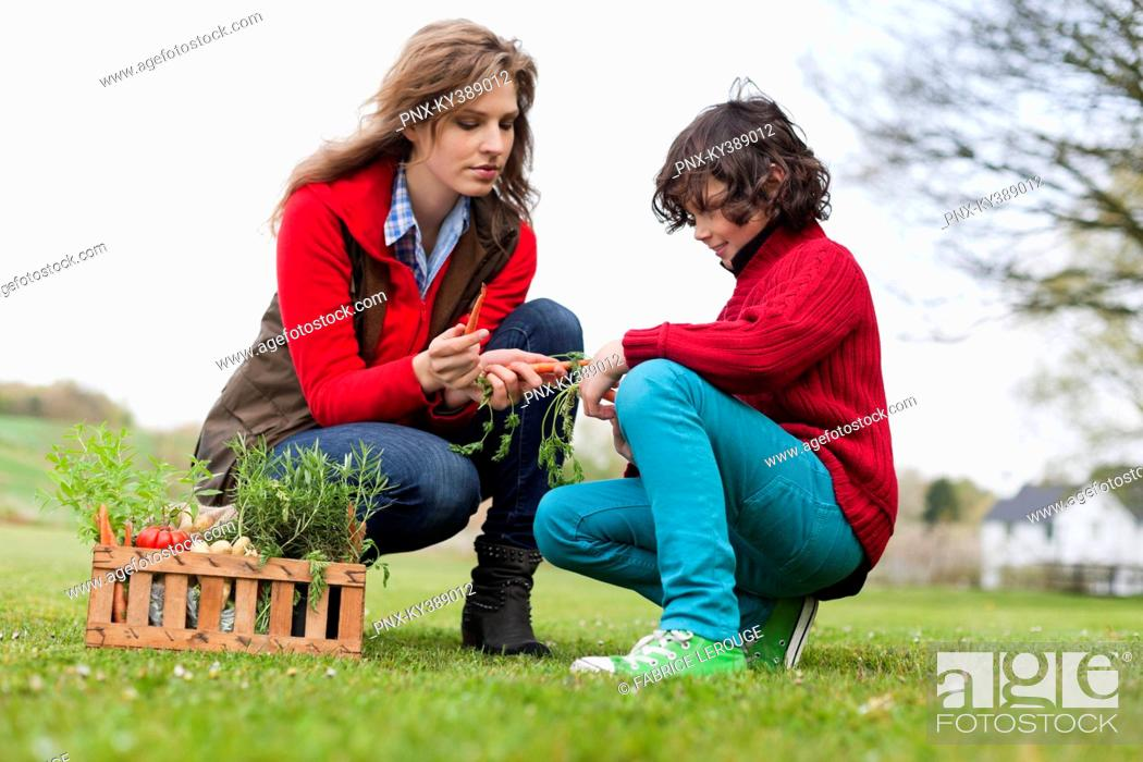 Stock Photo: Woman and son looking at vegetables in a park.