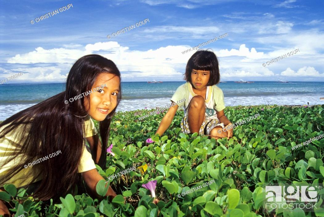 Stock Photo: Indonesian little girls picking flowers on the beach, Sumatra island, Republic of Indonesia, Southeast Asia and Oceania.