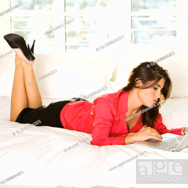Stock Photo: Businesswoman lying on the bed using a laptop.